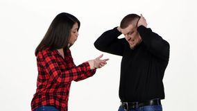 Quarrel between man and woman. Isolated on white background. The woman begins to sort things out with a man, he is angry and shuts his ears hands, on white stock footage