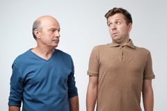 Quarrel between mature father and adult son stock images
