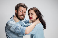 The quarrel men and women. The quarrel and strangling men and women on gray background Stock Photography