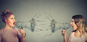 Quarrel between two women screaming at each other in megaphone Royalty Free Stock Photo