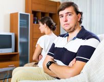 Quarrel woman and man. Portrait of sad wife and young husband in home interior stock images