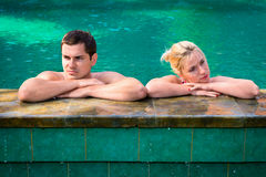 Quarrel between young couple in vacation. Quarrel in vacation: angry and exasperated young couple in a swimming pool on a poolside in tropical resort stock images
