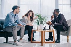 Quarreling couple talking to african american psychiatrist. In office Royalty Free Stock Photography