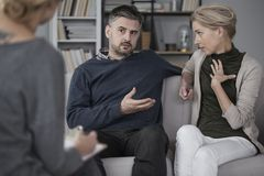 Quarreling couple with therapist. Quarreling couple on a grey sofa with therapist writing notes Royalty Free Stock Images