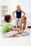 Quarreling and fighting kids. With their puzzled mother in background Royalty Free Stock Photos