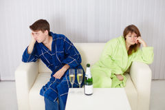 Quarrelled husband and wife at house on sofa Stock Images