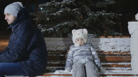 Quarrelled parents sit backs to each other with daughter on bench in winter park stock video