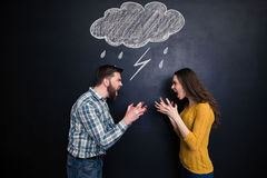Quarrelling couple standing against background of chalkboard and screaming. Quarrelling young couple standing against background of chalkboard and screaming on Royalty Free Stock Photography