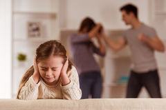 Quarrels upset child. Ð¡hild suffering from quarrels between parents in the family at home royalty free stock photo