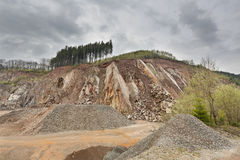 Quarry in the Ardennes, Belgium. A large quarry in the Ardennes, Belgium with dark clouds, a rest of forest on the hill top Royalty Free Stock Image