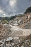 Quarry in the Ardennes, Belgium. Road through a large quarry in the Ardennes, Belgium with dark clouds, a rest of forest on the hill top Royalty Free Stock Photography