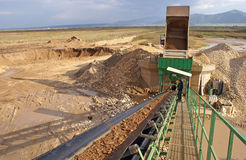 Quarry conveyor. Truck unloading gravel into quarry conveyor Royalty Free Stock Image