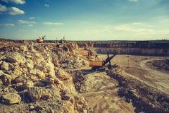 Quarry equipment, excavator, heavy vehicles work in quarry. Toned stock photo