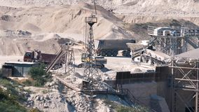 Quarry for the extraction of flux limestone. The work of trucks and conveyor in a quarry for the extraction of flux limestone stock footage