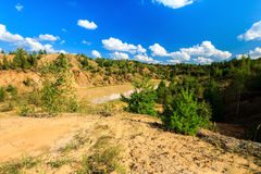 Quarry or lake or pond with sandy beach, brown dirty water, tree Stock Photo