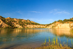 Quarry or lake or pond with sandy beach, green water, trees and. Hills with blue sky at summer season Stock Images