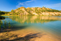 Quarry or lake or pond with sandy beach, green water, trees and. Hills with blue sky at summer season Royalty Free Stock Photos