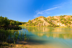 Quarry or lake or pond with sandy beach, green water, trees and. Hills with blue sky at summer season Stock Photo
