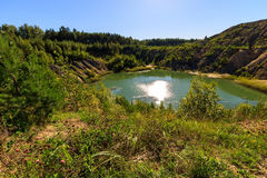Quarry or lake or pond with sandy beach, green water, trees and. Hills with blue sky at summer season Stock Image