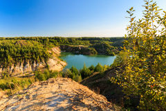 Quarry or lake or pond with sandy beach, green water, trees and. Hills with blue sky at summer season Royalty Free Stock Image