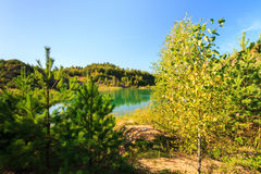 Quarry or lake or pond with sandy beach, green water, trees and. Hills with blue sky at summer season Stock Photos