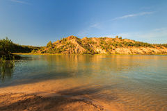 Quarry or lake or pond with sandy beach, green water, trees and. Hills with blue sky at summer season Royalty Free Stock Photography
