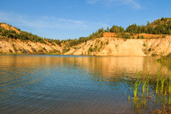 Quarry or lake or pond with sandy beach, green water, trees and. Hills with blue sky at summer season Royalty Free Stock Images