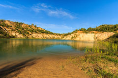 Quarry or lake or pond with sandy beach, green water, trees and. Hills with blue sky at summer season Stock Photography
