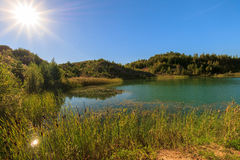 Quarry or lake or pond with sandy beach, green water, trees and. Hills with blue sky and sun at summer season Stock Photo