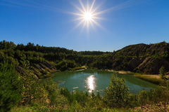 Quarry or lake or pond with sandy beach, green water, trees and. Hills with blue sky and sun at summer season Royalty Free Stock Images