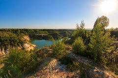 Quarry or lake or pond with sandy beach, green water, trees and. Hills with blue sky and sun at summer season Royalty Free Stock Photo