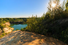 Quarry or lake or pond with sandy beach, green water, trees and. Hills with blue sky and sun at summer season Royalty Free Stock Image