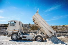 Quarry truck unloads white limestone gravel to crushed stone quarry stock image