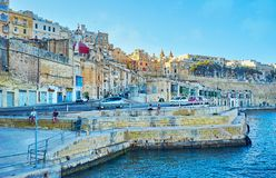 The Quarry Wharf, Valletta, Malta. VALLETTA, MALTA - JUNE 17, 2018: The ferry terminal at Quarry Wharf with a view on medieval waehouses, fortress wall and Royalty Free Stock Photos