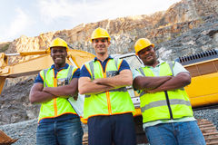 Quarry workers. Group of quarry workers standing next to excavator with arms crossed Royalty Free Stock Image