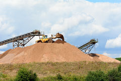Quarry working machinery creating piles of stones Royalty Free Stock Photography