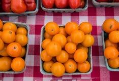 Quart round pomarańczowi czereśniowi pomidory na szachownica bielu i czerwieni tablecloth zdjęcia royalty free