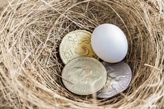 Quarter dollar coin, British one pound, and euro coin with the e. Gg in bird`s nest. The concept of business growth, financial or trade Stock Images