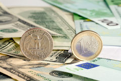 Quarter dollar and euro. On banknotes background royalty free stock images