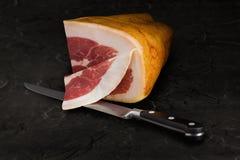 Iberico Ham. A quarter of iberico ham, mid sliced and knive on a slate plate Stock Photo