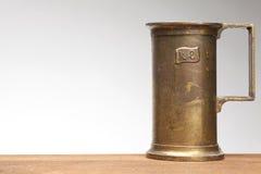 Quarter liter measure. Quarter liter brass measure on white background Stock Image
