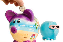 Quarter Into Piggy Bank Stock Photo