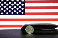 A quarter of US Dollar coins on obverse USD and black wallet on black floor with American flag background. royalty free stock photos