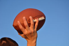 Quarterback Passing an American Football. Quarterback Throwing an American Football Against a Blue Sky Stock Images
