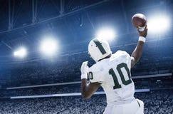 Quarterback som kastar en fotboll i en lek för yrkesmässig fotboll arkivbild
