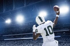 Quarterback throwing a football in a professional football game. The veiw from behind of an african American football quarterback throwing the ball downfield in Stock Photography