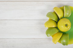 Quartered apples laid out around the whole apple on a saucer, placed with copy space. royalty free stock image