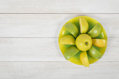Quartered apples laid out around the whole apple on a saucer, placed with copy space. stock images