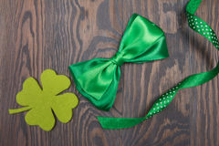 Quarterfoil clover and green bow tie. St. Patricks Day. Quarterfoil clover and green bow tie on wooden brown background. St. Patrick `s Day. Traditional Irish Stock Image