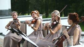 Quartet musical Trois violonistes et violoncelliste jouant la musique Tir moyen clips vidéos